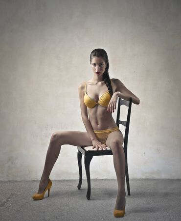 white people: Beautiful model sitting on a chair Stock Photo