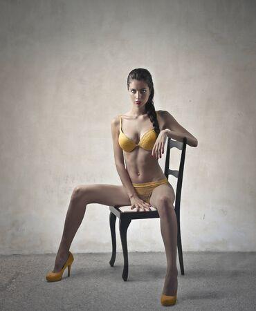 woman underwear: Beautiful model sitting on a chair Stock Photo