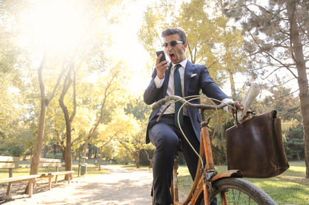 gaff: Businessman riding bicycle at the park Stock Photo