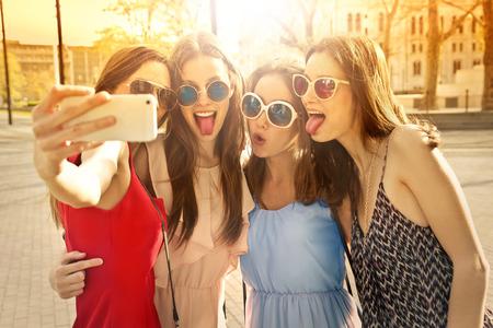 Vier lächelnde Mädchen, die eine selfie Lizenzfreie Bilder