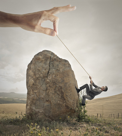 help: Businessman trying to climb a rock with the help of a giant hand