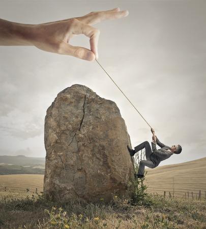 El hombre de negocios tratando de subir una roca con la ayuda de una mano gigante Foto de archivo
