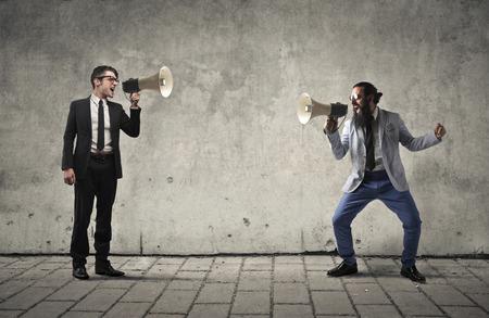 Los hombres de negocios gritando por megáfono