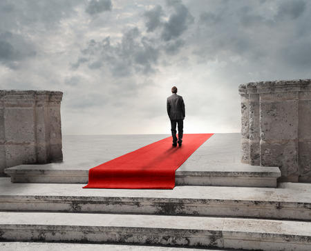 Businessman walking on a red carpet leading to nowhere