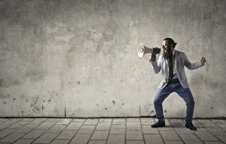 Businessman screaming into a megaphone Foto de archivo