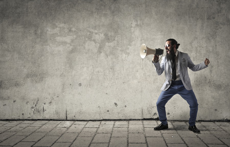Businessman screaming into a megaphone Stockfoto