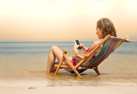 teen bikini: Young woman sending a text message while sitting at the beach Stock Photo