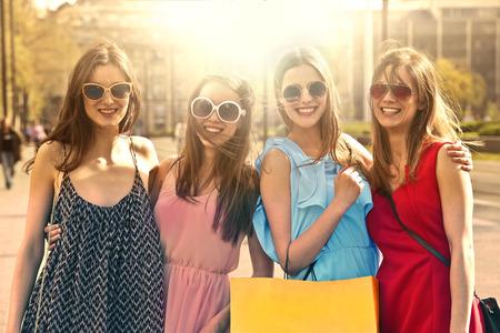 Vier lachende vrienden gaan samen Stockfoto