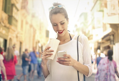 drinking: Young woman walking in the street with milkshake and smartphone