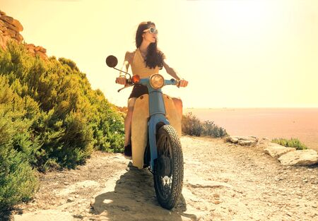 vacation: Young woman driving a moped Stock Photo