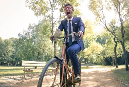 gaff: Young businessman riding a bike Stock Photo