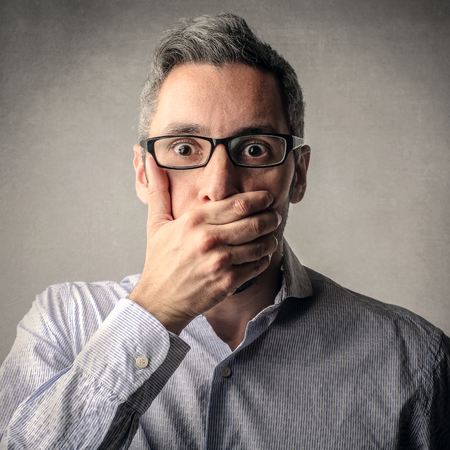 in shock: Shocked man covering his mouth with his hand