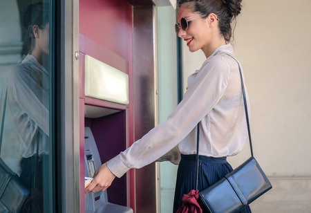 withdraw: Young woman doing a money withdrawal Stock Photo