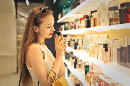 makeup: Young woman choosing a perfume Stock Photo