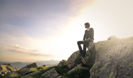 detach: Man sitting on a rock in the sunshine Stock Photo