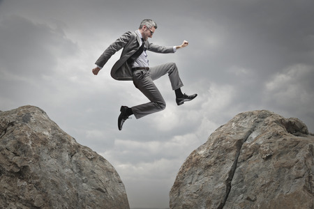 businessman jumping: Businessman jumping from a rock to another Stock Photo