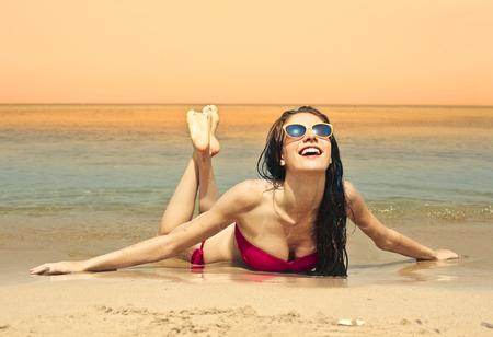nadar: Bella mujer tumbada al sol en la playa