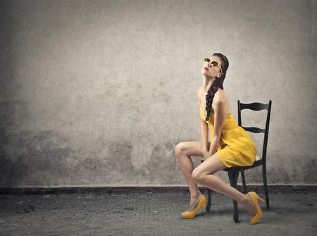 mode: Vrouw draagt een gele jurk zittend op een stoel Stockfoto