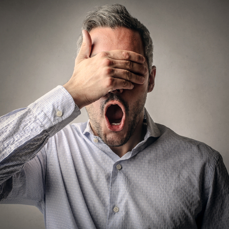 Shocked man covering his eyes with his hand