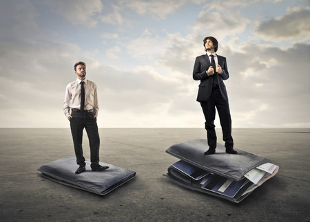 poor man: Two businessmen standing on a flat and a full wallet
