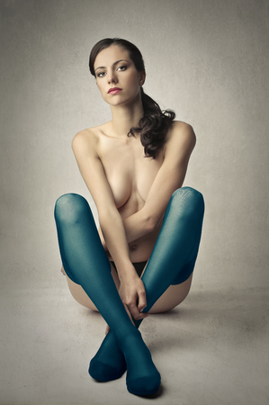nude girl sitting: Woman wearing blue stockings Stock Photo