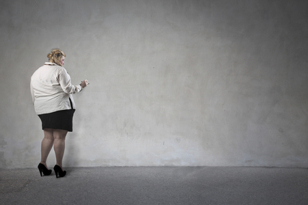 sad lady: Chubby woman writing on a blank wall Stock Photo
