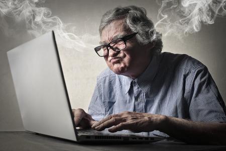 enojo: Hombre mayor que usa la tecnolog�a