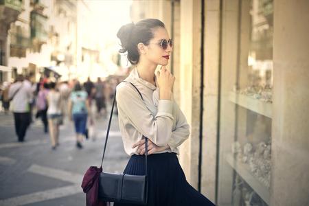 Elegante vrouw op zoek naar het raam van een winkel Stockfoto
