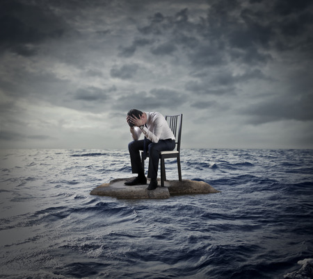 unhappy man: Desperate businessman sitting on a chair in the middle of the ocean