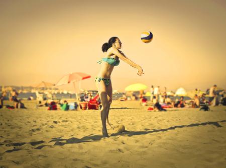 pelota de voley: Mujer joven que juega voleibol de playa