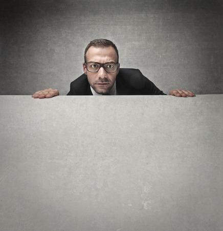 face work: Businessman hiding behind a table