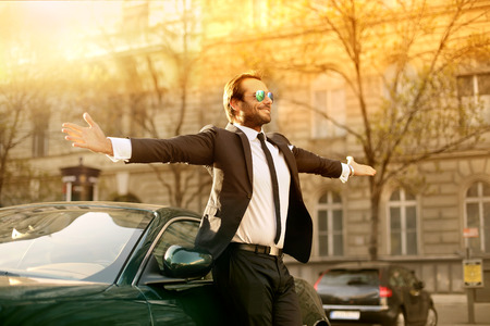 Homme d'affaires prospère debout à côté de sa voiture chic