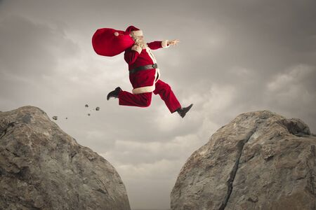 Santa Claus jumping from a rock to another Stock Photo