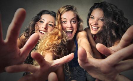 mujeres felices: Tres chicas excitadas que intentan llegar a algo Foto de archivo