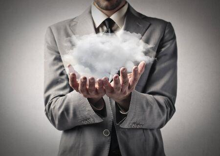 solution: Businessman holding a cloud