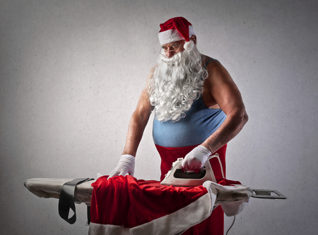 santa claus: Santa Claus doing the ironing