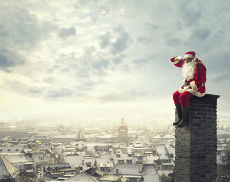 to santa: Santa Claus on a chimney Stock Photo