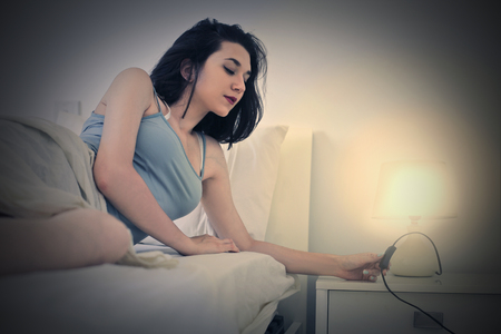 lady with the lamp: Woman going to sleep Stock Photo