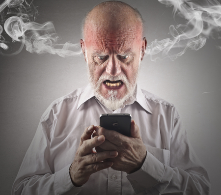 Furious man trying to use a smartphone