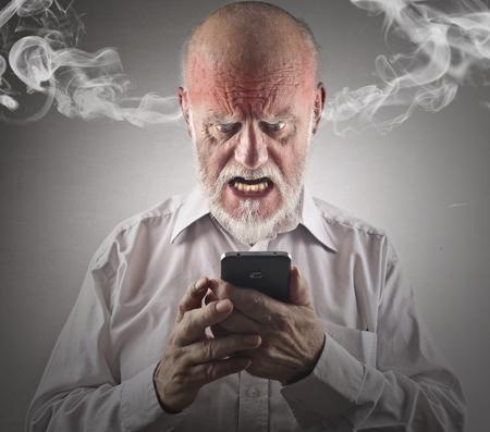 Woedende mens probeert om een smartphone te gebruiken Stockfoto