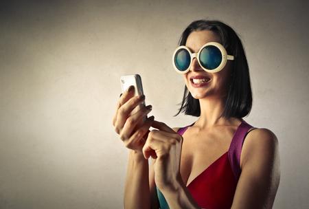 loco: Mujer sonriente que usa un teléfono inteligente Foto de archivo