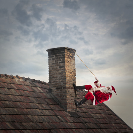 Santa Claus climbing on a chimney Stock Photo