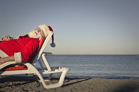 Santa Claus sleeping at the beach Stock Photo