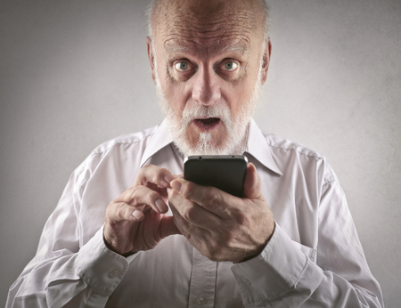 white beard: Man trying to use a smart phone