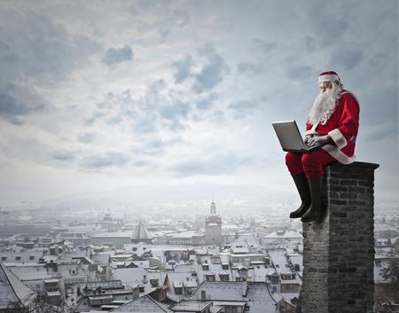 De Kerstman op de top van een schoorsteen Stockfoto
