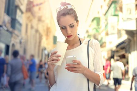 Mujer con la bebida suave y teléfono inteligente Foto de archivo