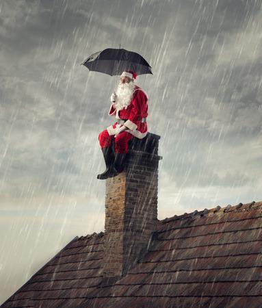 Kerstman onder de regen Stockfoto