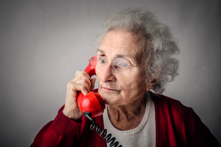 landline phone: Grandmother using a red phone