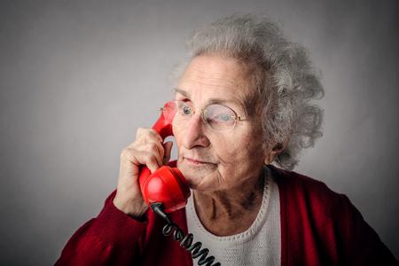 La nonna utilizzando un telefono rosso Archivio Fotografico - 47840635