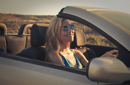cabrio: Smiling woman driving a car